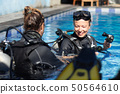 Woman getting first experience with scuba diving under the guidance of experienced recreational 50564610
