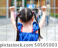 Closeup Child girl holding steel fence. Rear view. 50565003