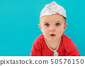 Baby in a foil hat sits on a blue background 50576150