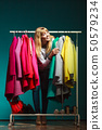 Woman choosing clothes to wear in mall or wardrobe 50579234