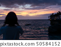 紅色的雲和波浪的地平線突出顯示的日落場景是由一個女孩在智能手機上拍攝的 50584152