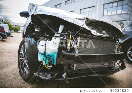 Broken and crashed modern car after an accident on street 50584880
