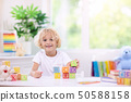 Child learning letters. Kid with wooden abc blocks 50588158