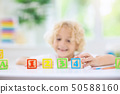 Child learning letters. Kid with wooden abc blocks 50588160