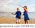 Kids blow bubble at beach. Child with bubbles 50588161