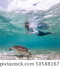 Woman on vacations wearing snokeling mask swimming with sea turtle in turquoise blue water of Gili 50588167