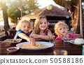 Family vacation lunch. Kids in beach restaurant 50588186