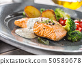 Roasted salmon fillet broccoli tomatoes and fried 50589678