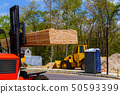 Aerial view a construction fork lift truck. driver outside a lifting and moving pallet 50593399