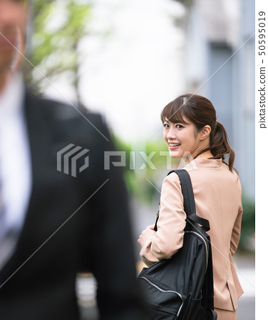 Young men and women passing each other on the street 50595019