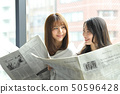 Two women reading a newspaper on the window side 50596428