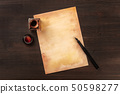 A vintage background with a nib pen on a piece of old paper, with an ink well, shot from above on a 50598277