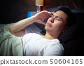 asian man in bed suffering insomnia and headache 50604165