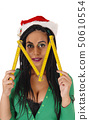 Woman holding a zollstock in front of her face 50610554