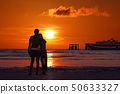 Mother and daughter look at sunset on the beach. 50633327