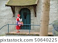 Little Red Hood near the door of a house in Theme Park Efteling. Spring. 50640225