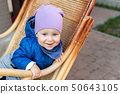 Portrait of cute adorable caucasian baby boy having fun sitting in wooden rattan rocking chair on 50643105
