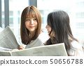 Two women reading a newspaper on the window side 50656788