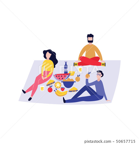 Group of young people having picnic outdoors with food on blanket 50657715