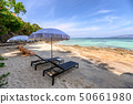 Umbrella with wooden sunbed on the white beach at 50661980
