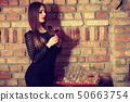 Woman tasting wine in rural cottage interior 50663754
