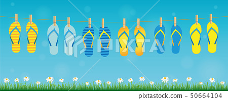 colorful pattern flip flops hanging on a rope on turquoise background with green grass and daisy 50664104