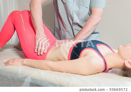 Male manual visceral therapist masseur treats a young female patient. Edit the internal organs and 50669572