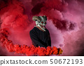 Devil with scary mask surrounded by red smoke 50672193