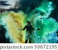 Devil with scary mask surrounded by coloured smoke 50672195