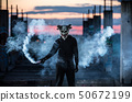 Devil with scary mask surrounded by white smoke 50672199