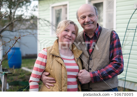 Mature european couple embracing in front of house 50678005