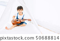 Little kid learning to play a music (guitar)  50688814