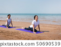 Women practicing yoga on the beach 50690539