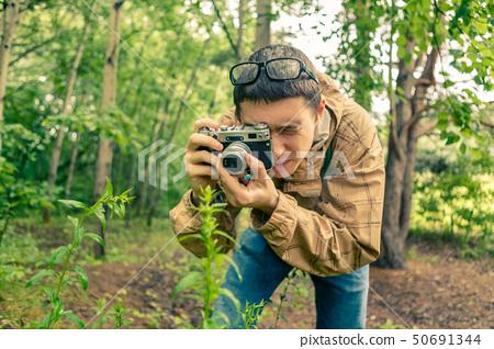 Guy biologist in glasses photographs plants 50691344