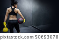 Asian girl holding basketball and kettlebell 50693078
