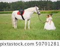 little princess with white horse in summer field 50701281