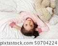 cute little child girl in pyjamas with teddy bear 50704224