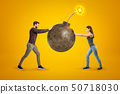 Young man and woman in casual clothes holding big ball bomb with fuse on yellow background 50718030