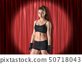 Front crop view of young woman in black crop top, shorts and fingerless gloves standing in spotlight 50718043