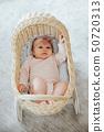 newborn in a toy wicker trolley, top view 50720313