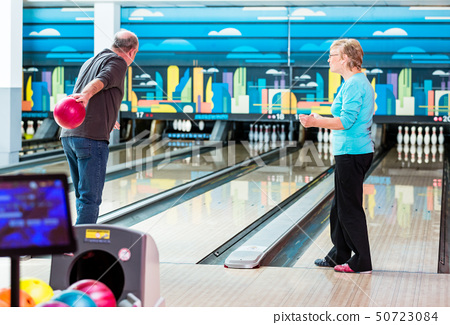 Rear view of a mature man bowling 50723084