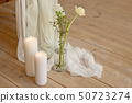 Branch of blooming white peony tulip Mattiola branch in a glass vase white wax candles stand on the 50723274