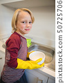 Boy washing utensil in kitchen 50725706
