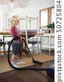 Boy using vacuum cleaner in living room 50725804