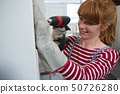 Female carpenter using drill machine 50726280