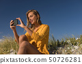 Woman taking selfie with mobile phone at beach 50726281