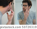Man looking his face in mirror 50726319