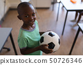 Smiling schoolboy holding football in classroom 50726346