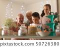 Multi-generation family celebrating birthday of grandson 50726380