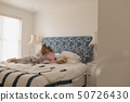 Mother with her daughter reading storybook in bedroom 50726430